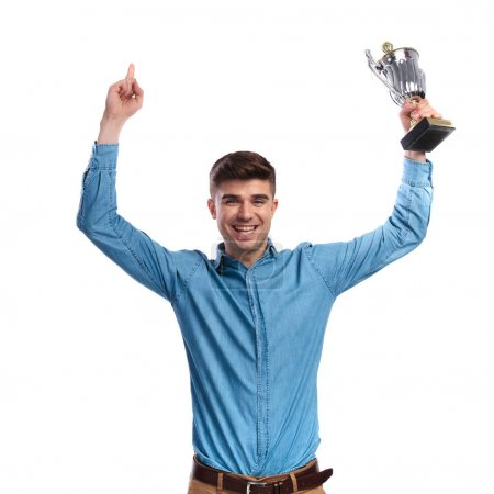 man celebrating success while holding trophy cup in the air