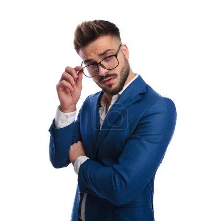 Photo pour Portrait d'un smart casual homme séduisant fixant ses lunettes qui est sceptique au sujet de quelque chose, debout sur fond blanc - image libre de droit