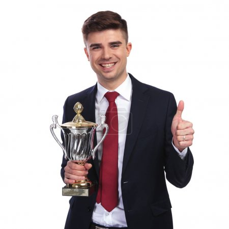 portrait of young businessman holding trophy and making ok sign