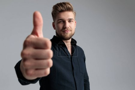 Photo for Positive fashion man giving a thumbs up while wearing a black shirt and red jeans, standing on gray studio background - Royalty Free Image