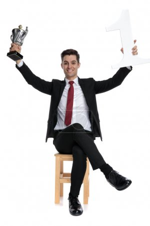 Photo pour Homme d'affaires prospère célébrant avec son trophée et tenant un numéro un tout en portant un costume noir et cravate rouge, assis sur une chaise sur fond de studio blanc - image libre de droit