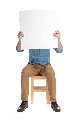 Photo pour Jeune mec décontracté se cachant derrière une planche vide et assis isolé sur fond blanc, plein corps - image libre de droit