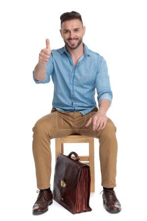 Photo pour Jeune homme occasionnel souriant en train de faire des pouces vers le haut, assis isolé sur fond blanc, plein corps - image libre de droit