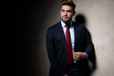Photo for Cool formal guy wearing navy suit standing and fixing his jacket while looking away happy on gray studio background - Royalty Free Image