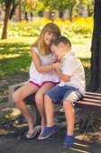 Little boy and little girl playing in the park on the bench on sunny summer day