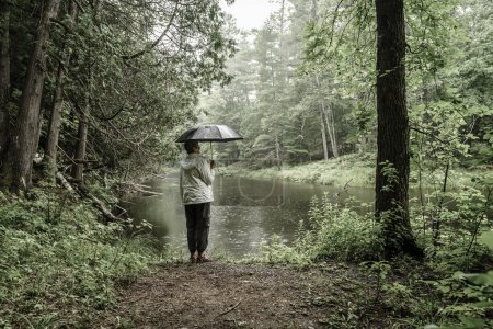 Woman with umbrella standing on a river bank