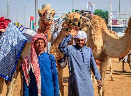 Photo pour Dubaï, Émirats arabes unis - 25 mars 2016 : Les manutentionnaires de chameaux sourient avec leurs animaux au Dubai Camel Racing Club - image libre de droit