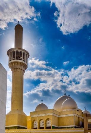 Minaret of a mosque in Bur Dubai backlit by the sun.