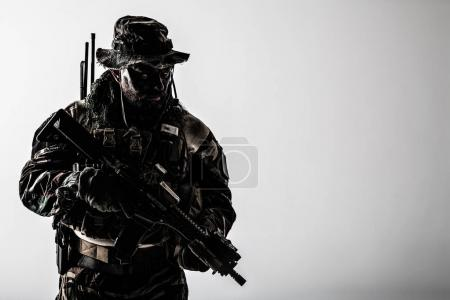 Foto de Estados Unidos, las fuerzas especiales en uniformes de camuflaje estudio tiro. Tenencia de armas, usa sombrero de selva, Shemagh bufanda, cara pintada, que está listo para matar. Contraste oscuro - Imagen libre de derechos