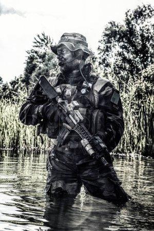 Foto de Barbudo soldado de fuerzas especiales en acción durante la incursión de río en el terreno de la selva. Es cintura profundo en el agua y el barro y con ganas de conocer a enemigo, sobrevivir y luchar en el agresivo ambiente hostil - Imagen libre de derechos