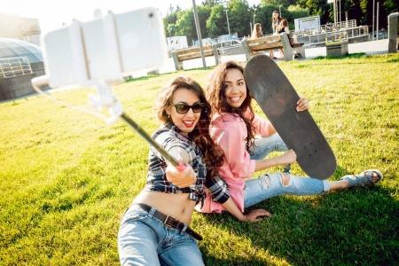 Two young mixed race girls doing selfie with skate...