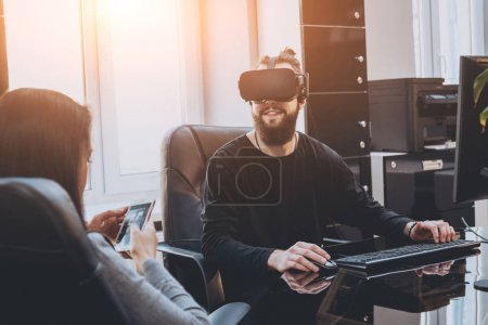 Young man with woman creative office workers testing VR goggles and having fun