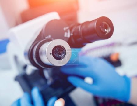 Microscope with metal lens at laboratory. Medical equipment
