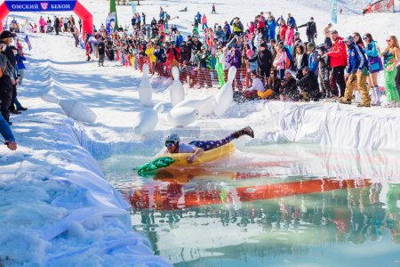 Sheregesh, Kemerovo region, Russia - April 13, 2019: Pool and ride contest where people on a swimming ring playing huge bowling on the snowy slope next to the pool.