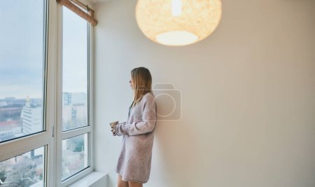 beautiful girl in a green socks and long pale purple sweater with a cup of tea looking to the window, home, comfort, happiness