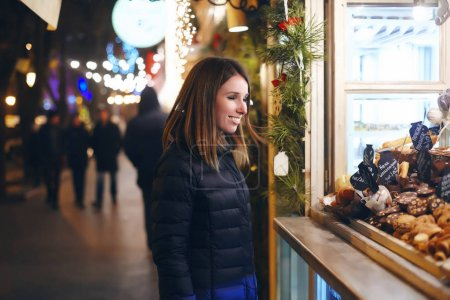 beautiful girl stands and smiles in the street next to the coffee shop, which is decorated with beautiful garlands, Christmas parties, New Year's holiday