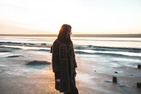Girl in a coat walks on the lake
