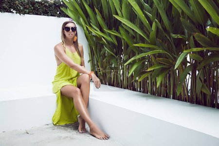 Beautiful sexy young brunette woman with long wavy hair thin slender figure perfect body and pretty face make-up wearing a yellow evening dress and jewelry.summer accessory,design dress collection