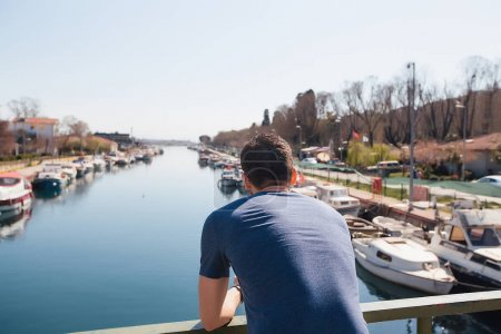 Photo for Back portrait Handsome guy standing on the bridge.Strong man on a bridge.Casual man's wear.Beautiful view from a bridge. - Royalty Free Image