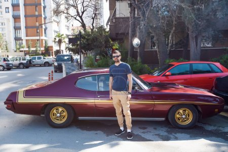 Man standing near retro car.