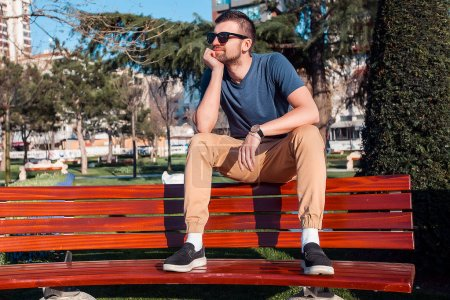 Photo for Handsome man in sunglasses sitting on bench in park - Royalty Free Image