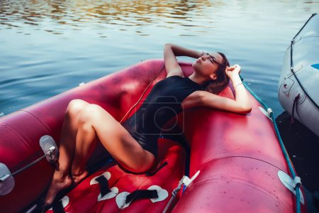 blonde woman in red Inflatable boat