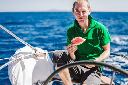 guy   with a watermelon n the yacht