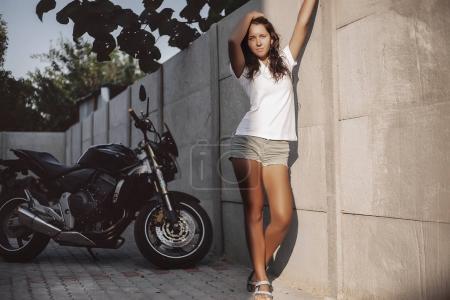 woman standing near black motorcycle