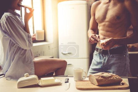 Photo for Cropped image of beautiful young passionate couple eating toasts and drinking coffee in kitchen at home - Royalty Free Image