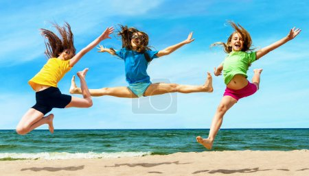 Happy active childrenl jumping at the beach