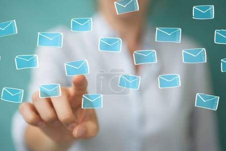 Photo for Businesswoman on blurred background holding and touching floating emails sketch - Royalty Free Image