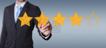Photo pour Homme d'affaires sur la cote d'arrière-plan flou avec main dessiné des étoiles - image libre de droit