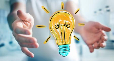 Businessman holding and touching a lightbulb sketch