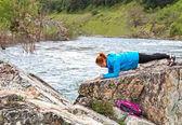Girl Doing a Plank on Rocks Near Fast River