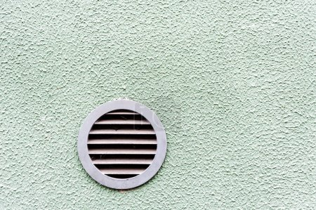 circular plastic air vent in white green wall ventilation grille
