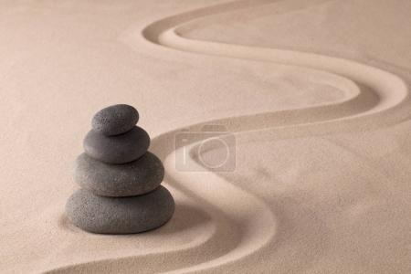 balancing black rocks in zen sand garden