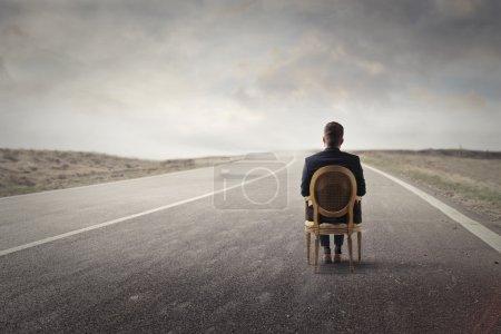 Photo pour Homme d'affaires est assis sur une chaise sur la route - image libre de droit