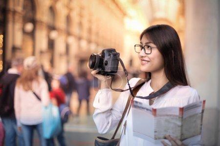 Photo pour Femme asiatique avec un guide et une machine à photo - image libre de droit