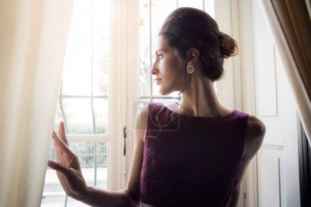 Photo pour Femme est debout devant la fenêtre - image libre de droit