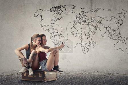 Photo pour Deux filles assises dans un coffre avec une carte du monde en arrière-plan - image libre de droit