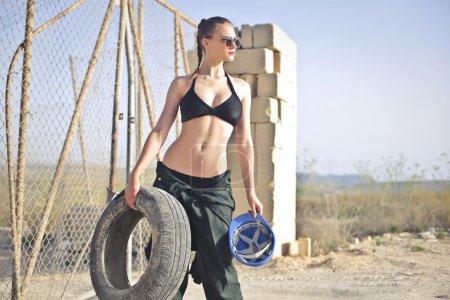 Photo pour Femme avec un pneu dans ses mains - image libre de droit