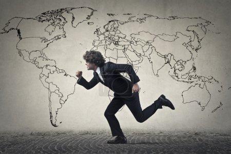 Photo pour Homme running imitant en face d'un carte du monde - image libre de droit