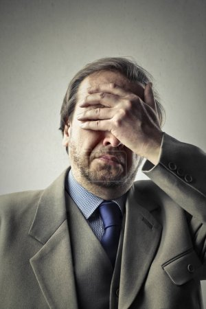 Photo for Businessman holding his head while making sad face - Royalty Free Image