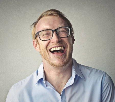 Photo pour Homme d'affaires avec des lunettes riant dans la chambre - image libre de droit