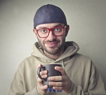 Nerdy man holding a cup inside
