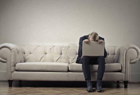 Tire businessman sleeping on his laptop