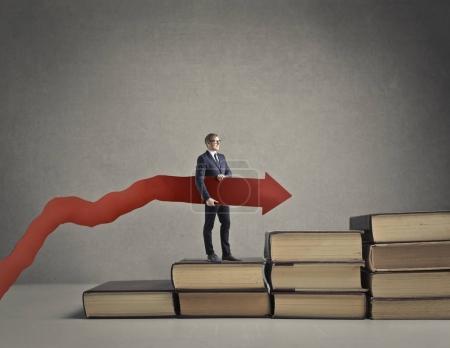 Photo pour Homme d'affaires avec flèche debout sur les livres - image libre de droit
