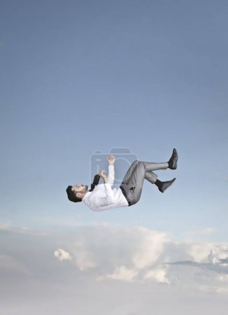 Young businessman falling in the sky