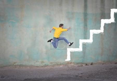 Man jumping on drawn stairs