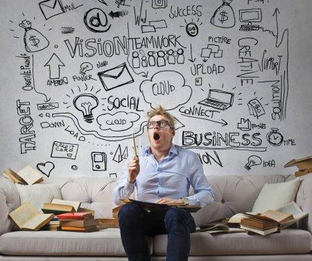 Photo pour Jeune homme d'affaires ayant beaucoup d'idées sur le canapé - image libre de droit
